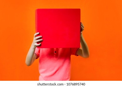 funny boy holding a box on an orange background
