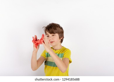 Funny boy playing with red slime looks like gunk