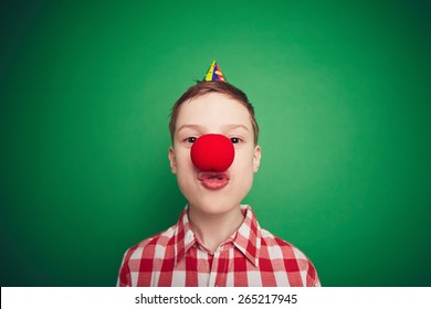 Funny boy with red clown nose looking at camera at foolâ??s day celebration