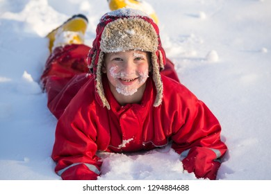 Funny boy with snow on his face at the winter outdoors