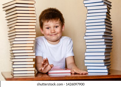 funny boy and stacks of books. cheerful child is a first grader indoors