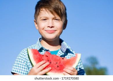 Funny boy with watermelon against blue sky in summer park, healthy food
