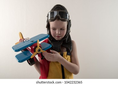 Funny boy in yellow overalls and  hat, in a red scarf and pilot's goggles, sits on vintage suitcase with an airplane model and dreams of adventures. The concept of travel romance and discovery