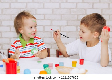 funny boys Caucasian children paint with bright colors, get dirty and dirty each other and have fun, paint Easter eggs with bright colors, the concept of education and leisure.