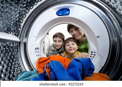 Funny boys and mother loading clothes to washing machine. View from the inside of washing machine.