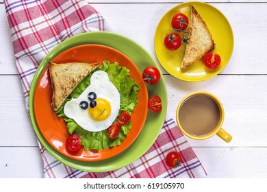 Funny Breakfast with bear-shaped fried egg, toast, cherry tomato, lettuce on colored plates and coffee. Top view.