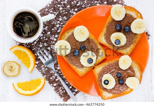 Petit-déjeuner amusant pour les enfants - toast au chocolat, banane et baies en forme d'ours. Idée créative d'art culinaire pour les enfants vue de dessus