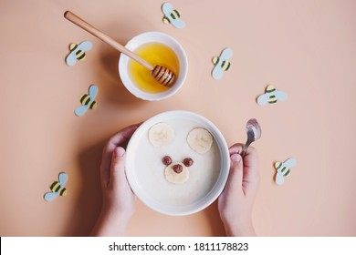 Funny breakfast food for kids. Creative baby porridge in the form of a bear, with banana, honey and bees on the background. Baby food menu.