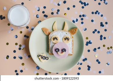 Funny breakfast toast for kids. Creative children's sandwich in the shape of a bull, served with a glass of milk. Baby food menu. Symbol of the year 2021