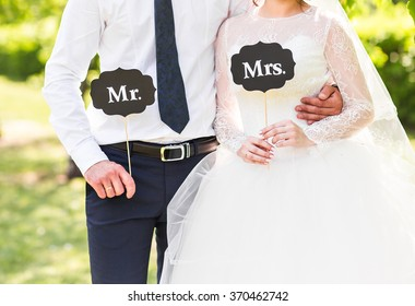 Funny bride and groom with Mr and Mrs signs. Happy wedding day