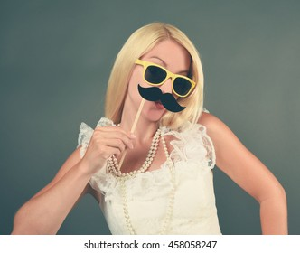 A funny bride with a vintage white dress is holding a mustache photo booth prop for a humor or love concept.