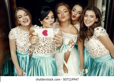 Funny bridesmaids and bride take selfie on the iPhone