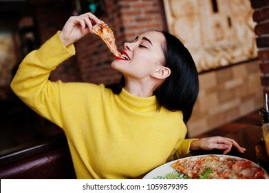 Funny brunette girl in yellow sweater eating pizza at restaurant.  - Shutterstock ID 1059879395