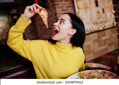 Funny brunette girl in yellow sweater eating pizza at restaurant.