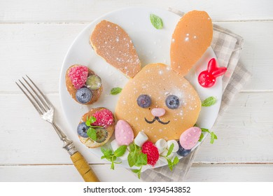 Funny bunny pancakes, Cute Kids Breakfast for Easter morning. Creative rabbits pancakes with fresh berry decoration, top view on white wooden background copy space