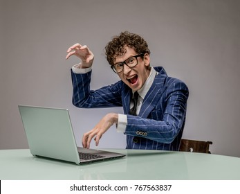 Funny business man geek using laptop with evil genius facial expression