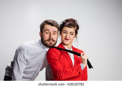 The funny business man and woman cooperating on a gray background. Business concept of leadership of colleagues