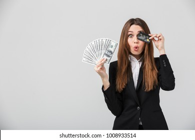 Funny businesslady grimacing and holding cash and credit card in hands isolated over grey
