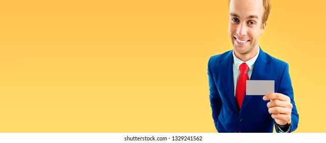 Funny businessman in blue suit and red tie, showing blank business or plastic credit card with copy space area for some text or slogan, over yellow-orange color background, wide horizontal composition