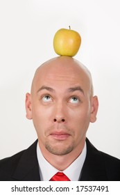 Funny businessman having apple on his head and looking at it