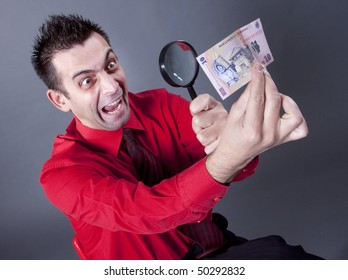 Funny businessman looking at banknote with magnifying glass