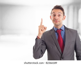 Funny businessman pointing his finger up while looking at you
