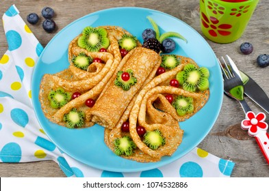 Funny Butterfly face pancakes with berries and fruits for kids' snack food. Creative breakfast idea for kids