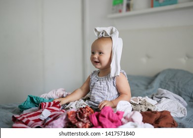 Funny Caucasian baby 10 months playing with a bunch of clothes, a mess and children, motherhood and mom do not have time, rummaged at home. Bright bedroom interior