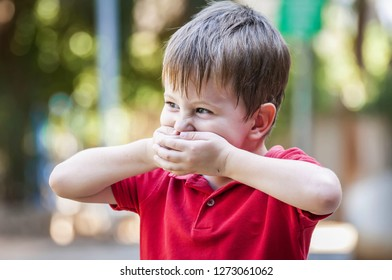 Funny Caucasian child closing his mouth to hide a smile in the park outside in the summer. Laughing positive child, happy childhood concept lifestyle, child about to laugh.