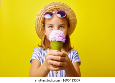 Funny caucasian child girl with ice cream, close-up shot on yellow isolated background.