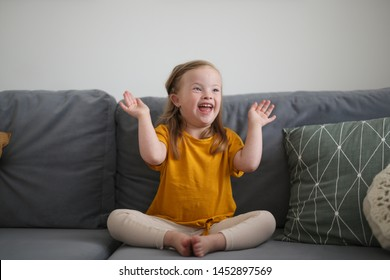 Funny Caucasian girl child with Down syndrome on a sofa in a bright modern interior room