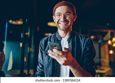 Funny caucasian male in casual wear laughing at content from social networks using mobile phone, positive millennial generation hipster guy satisfied with tariffs for 4G internet on smartphone