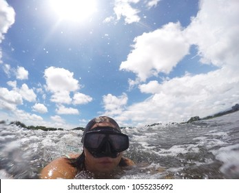 Funny caucasian woman wearing a mask for snorkeling in the ocean and making selphie. Her face is funny distorted