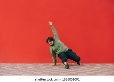 Funny charismatic overweight man dancing breakdance on red wall background, wearing casual clothes. Fat guy dancing hip hop on the street on a red background