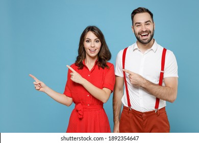 Funny cheerful young couple two friends man woman wearing white red clothes pointing index fingers aside isolated on pastel blue color background studio portrait. Valentine's Day holiday concept
