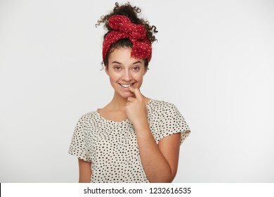 Funny cheerful young girl with curly hair flirtatiously holds her finger at the open mouth, seduces, looks dolly with headband, isolated over a white background