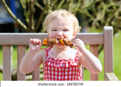 Funny child, adorable blonde toddler girl in red dress messy around mouth eating delicious meat made on bbq sitting outdoors in the garden on a wooden chair on a sunny summer day