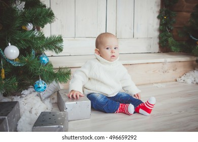 funny child with big blue eyes in red socks holding Christmas gift in hand. Christmas concept.