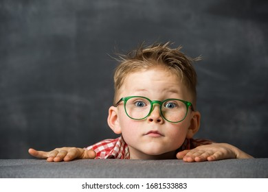 Funny child boy in glasses looks out with surprised face. School child hiding.