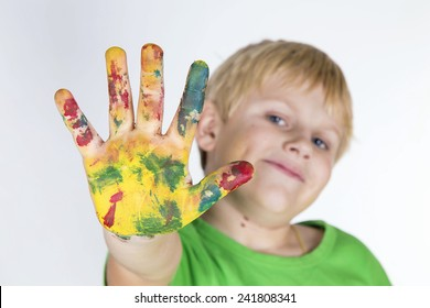 Funny child boy with hands painted with colorful paint