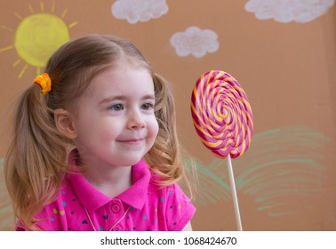 Funny child with candy lollipop, happy little girl eating big sugar lollipop, kid eat sweets. Beautiful little girl with lollipop