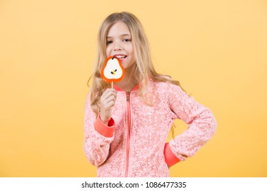 Funny child with candy lollipop, happy little girl eat big sugar lollipop, kid eat sweets. surprised child with candy on orange background.
