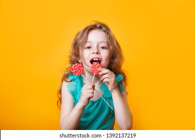 Funny child with candy lollipop, happy little girl eating big sugar lollipop on yellow bright background,