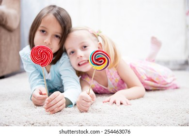 Funny child with candy lollipop, happy little girl eating big sugar lollipop