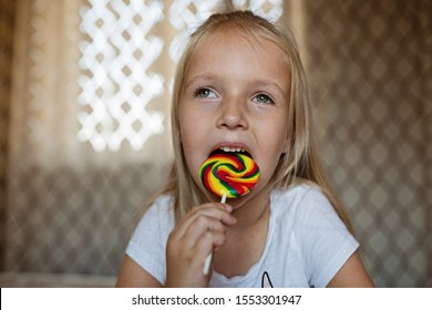 Funny child with candy lollipop, lifestyle photo of happy blonde little girl eating colorful sugar lollipop at home