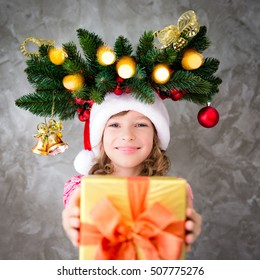 Funny child with Christmas tree branch giving gift box. Portrait of happy kid wearing Santa hat. Xmas holiday concept