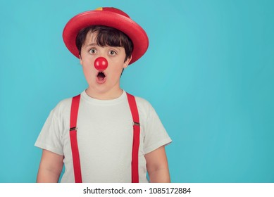 funny child with clown nose on blue background