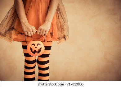Funny child dressed witch costume. Kid waiting candy with pumpkin container. Halloween autumn holiday concept