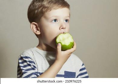 Funny Child eating apple.Little Boy. Health food. Fruits.Vitamin C
