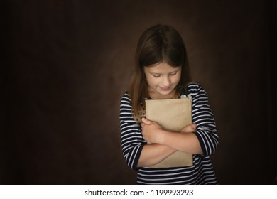 funny child girl with book in a craft cover on a dark brown background, concept child development